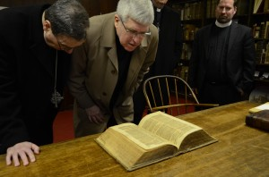 Father John Crossin (right, foreground) of the U.S. Conference of Catholic Bishops and the Rev. Dr. Robert Bugbee, president of Lutheran Church—Canada and vice-chairman of the International Lutheran Council, examine the personal Bible of J.S. Bach in the rare-book room of the Concordia Seminary, St. Louis, library. At right is the Rev. Dr. Albert Collver III. (LCMS Communications/Pamela J. Nielsen)