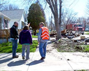 The Rev. Jacob Ehrhard (left), Tammy Fechner and Lutheran Early Response Team volunteer Andy Radetski talk among flood debris in Marseilles, Ill. (Lutheran Church Charities)