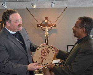 The Rev. Berhanu Ofgaa, general secretary of the Ethiopian Evangelical Church Mekane Yesus (right), presents a gift to LCMS President Rev. Dr. Matthew C. Harrison during a March 27, 2013, visit to St. Louis. (LCMS Communications/Frank Kohn)
