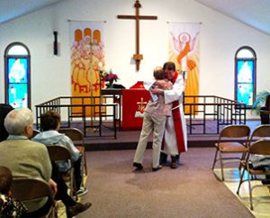 The Rev. Michael Dunne, pastor of St. Thomas Lutheran Church, Manalapan, N.J., hugs Lois Hinds, a member of the congregation, after presenting her with a check during the worship service on Sunday, May 19. (Nancy McGrath)
