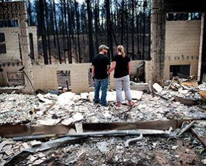 Jeremy and Kelly Beach look into the remains of their home off Ravine Drive on June 18 in Colorado Springs, Colo. Residents were allowed back into the area for a short time to view the properties that sustained the most damage from the fire. The Black Forest fire, the most destructive wildfire in Colorado history, has destroyed more than 500 homes and charred more than 22 square miles. (AP Photo/The Colorado Springs Gazette, Michael Ciaglo)