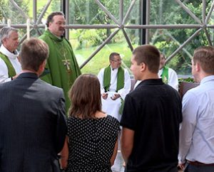 During the June 14 'sending service,' new LCMS missionaries and their family members (foreground) receive congratulations from (left to right) the Rev. Dr. Edward Grimenstein, director of LCMS Missionary Services; the Rev. Randy Golter, executive director of the LCMS Office of International Mission; and LCMS President Rev. Dr. Matthew C. Harrison. (LCMS Communications)