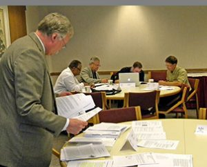 """LCMS Minnesota North District President Rev. Donald Fondow looks over documents for consideration by convention Floor Committee 3 for """"Life Together"""" that he chairs as a subcommittee works on resolutions. (LCMS Communications/Joe Isenhower Jr.)"""