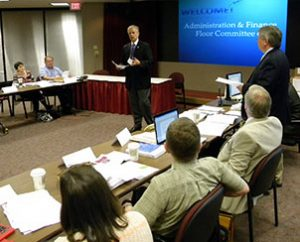 The Rev. Dr. Glen Thomas, executive director of LCMS Pastoral Education, provides comments for consideration by Floor Committee 6 for Administration and Finance. At right is the committee's chairman, the Rev. John Wille, president of the LCMS South Wisconsin District. (LCMS Communications/Joe Isenhower Jr.)