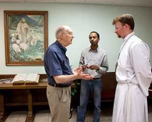 Vicar Aaron Uphoff, right, talks with Trinity Lutheran Church, Norman, Okla., prayer service attendees on May 22. (Dan Gill)
