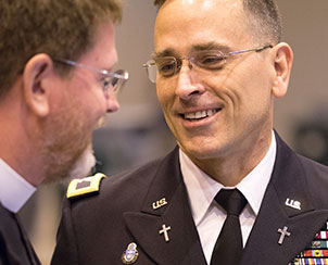 U.S. Army Chaplain Jonathan Shaw talks with the Rev. Tom Olson before Shaw addresses delegates about a resolution supporting religious and moral objections to women serving in ground combat.