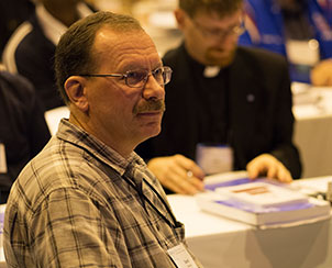 Delegates, including the Rev. Darrell Debowey from the Central Illinois District, listen to Floor Committee 7 propose amendments to Bylaws concerning structure and ecclesiastical matters.