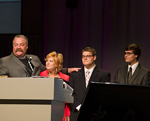 LCMS President Rev. Dr. Matthew C. Harrison, left, introduces his wife, Kathy, and the couple's sons, Matthew, left, and Mark, at the 65th Regular Convention of The Lutheran Church—Missouri Synod.