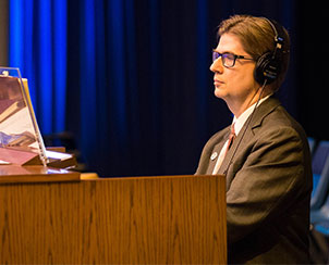 Cantor Phillip Magness uses headphones to rehearse on the organ while the convention is in session. (LCMS Communications)