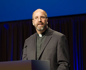 "The Rev. Dr. Steven P. Mueller delivers the fourth and final convention essay, ""Baptized for Life Together,"" Wednesday at the 65th Regular Convention. (LCMS Communications)"