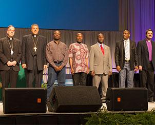 The convention recognizes visiting international Lutheran church leaders, from left, Rev. Dr. Robert Bugbee, Rev. Gennadij Khonin, Rev. Amos Bolay, Rev. Samuel S.Y. Navoh, Rev. James Kollie, Archbishop Christian Ekong and Bishop Vsevolod Lytkin. (LCMS Communications)