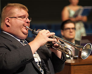 Matthew Janssen on trumpet and Cantor Phillip Magness on organ help lead the singing at a July 23 Matins service.