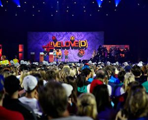 Concordia University, Nebraska, Seward, students give a shout-out to their school from the stage of the Alamodome in San Antonio before the July 1 opening night Mass Event that kicked off the 2013 National LCMS Youth Gathering. (Annie Sparks)