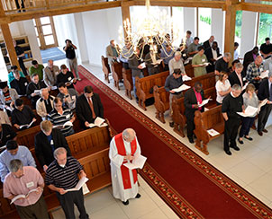 Participants of the Fifth World Seminaries Conference worship Aug. 11 in the closing Divine Service at the Palanga Lutheran Church and Diaconal Center in Palanga, Lithuania.  The Rev. Dr. Charles Evanson (front row, vested), an LCMS missionary and theological-education adviser for the Baltic countries, assisted for that service. (LCMS Communications/Amanda Booth)