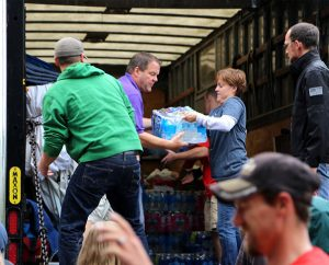 DCE Donna Patton of Peace with Christ Lutheran Church, Aurora, Colo., helps the Rev. Tim Runtsch, senior pastor of Redeemer Lutheran Church, Fort Collins, Colo., unload a case of bottled water Sept. 15. Members of Peace with Christ sent a truck with nearly 17,000 pounds of supplies to Fort Collins to help people who were displaced by floodwaters. (Redeemer Lutheran Church)