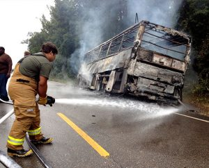 A firefighter aims a hose at the smoldering bus that caught fire as it was carrying football players and coaches from Concordia College Alabama, Selma, to a game at Miles College in Birmingham, Ala. All 62 passengers escaped without injury, but more than $70,000 of equipment was lost. (The Selma Times-Journal/Jay Sowers)