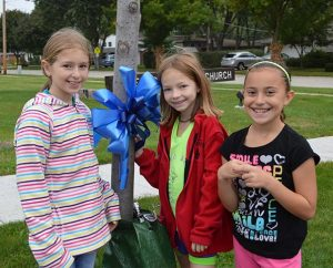 "Three third-grade students pose for a photo after tying a blue ribbon to a tree outside St. Peter Lutheran School, Arlington Heights, Ill., during an all-school celebration of St. Peter's ""National Blue Ribbon School"" status, which was announced Sept. 24, 2013. (St. Peter Lutheran School)"