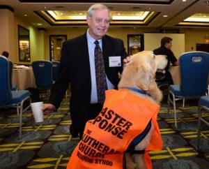The Rev. Glenn Merritt, director of LCMS Disaster Response, greets a Golden Retriever with the Lutheran Church Charities K-9 Comfort Dog Ministry at the 5th LCMS National Disaster Response Conference in St. Louis. During breaks at the Oct. 7-10 event, pastors knelt to pet and pose for pictures with the cuddly canines. (LCMS Communications/Amanda Booth)