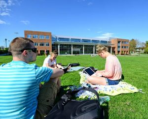 Students sit on the lawn in front of the library at Concordia University Portland in Portland, Ore. The school's enrollment grew by an astounding 74 percent — from 3,111 in 2012 to 5,428 this fall, an increase of 2,317 students — primarily because of its in online graduate programs. (Concordia University Portland)