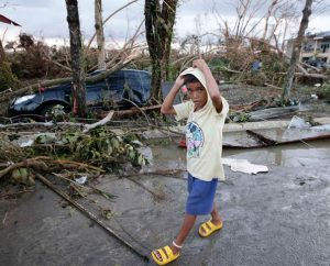 A boy walks past the devastation from powerful Typhoon Haiyan at Tacloban city, in Leyte province in central Philippines. Rescuers in the central Philippines initially counted at least 100 people dead and many more injured a day after one of the most powerful typhoons on record hit the region Nov. 8, wiping away buildings and leveling seaside homes with massive storm surges. (AP Photo/Bullit Marquez)