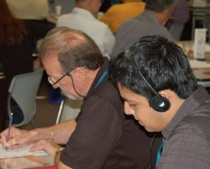 Cristian Morales, a lay leader at Cristo El Salvador Lutheran Church in Del Rio, Texas, listens on headphones to a simultaneous Spanish translation at the Partners in Latino Ministries Conference (PALMCON), Oct. 23-25 in El Paso, Texas. The Rev. Dr. Hector Hoppe, left, served as the conference chaplain. (John Williamson)