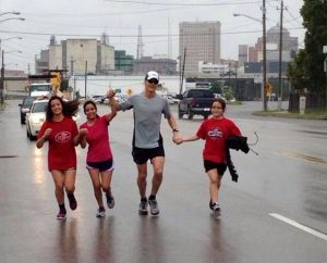 """The family of the Rev. Mark Junkans, executive director of LINC Houston, runs alongside him during the last leg of his 24-hour """"Run 4 the City"""" fundraiser that netted more than $80,000 for mission work. On the far left and right are daughters Victoria and Jessica, and second from left is Junkans' wife, Natalia. (LINC Houston)"""