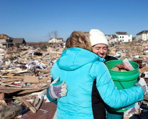 Shelly Goldammer smiles as Trudy Heren hugs her while they stand on what remains of Goldammer's house Monday, Nov. 18, 2013, in Washington, Ill. Goldammer and her family are members of Our Savior Lutheran Church in Washington. (LCMS Communications/Dan Gill)