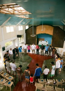 Members of the LCMS Disaster Response team pray with parishioners of Christ Lutheran Church in Mahayag, Leyte Province, in the Philippines during a closing worship service on Nov. 20. The church was badly damaged from Typhoon Haiyan. (LCMS Communications/Erik M. Lunsford)
