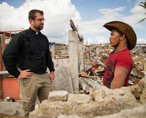 The Rev. Ross Johnson talks to resident Cris Megdue in Tacloban City.  (LCMS Communications/Erik M. Lunsford)