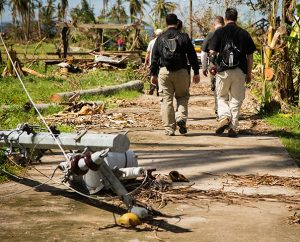Members of the LCMS Disaster Response team navigate around a downed power line while surveying in Mahayag, Leyte Province, the Philippines, on Nov. 18. (LCMS Communications/Erik M. Lunsford)