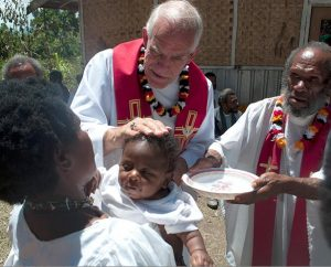 The Rev. Ron Rall, pastor of Timothy Lutheran Church in St. Louis and former missionary to Papua New Guinea, baptizes a baby on Aug. 26, 2011, during a visit to that country. At right is Bishop Philipo, a regional bishop of the Gutnius Lutheran Church, an LCMS partner church. Four congregations came together to celebrate 52 baptisms and 20 confirmations that day. Gifts to the Synod's Global Mission Fund are used to share the Gospel through missionaries and partner churches worldwide. (LCMS)