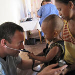 A volunteer treats a child during a 2009 Mercy Medical Team trip to Madagascar.