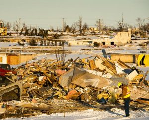 Workers gather near the rubble of a home in a damaged neighborhood of Washington, Ill., on Dec. 18, 2013. Nearly two dozen tornadoes plowed through Illinois in November, killing a total of seven people. (LCMS Communications/Erik M. Lunsford)