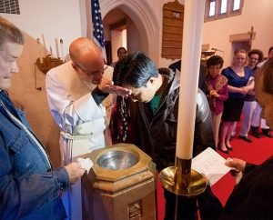 "The Rev. Matthew Clark baptizes Nepali immigrant Rana Tamang at Ascension Lutheran Church. ""It's not always comfortable, but it's a blessing,"" Clark said about the congregation's work with the Nepalese community. (LCMS Communications/Erik M. Lunsford)"