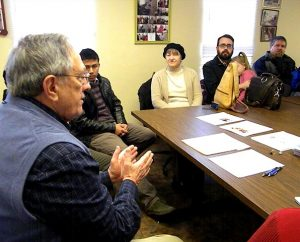 The Rev. Dr. Allan R. Buckman explains the ministry of Christian Friends of New Americans to the new missionary families during their orientation visit to that agency's St. Louis office Feb. 10. (LCMS Communications/Joe Isenhower Jr.)