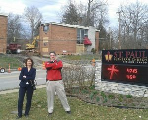 "Deaconess Sara Smith and the Rev. Steve Schave stand proud on the lawn of St. Paul Lutheran Church, Cincinnati — where they served at the time —on the day demolition began for the apartment complex known as the ""Devil's Playground.""  That day came to represent a revitalization for the neighborhood. (St. Paul Lutheran Church circa 2012)"