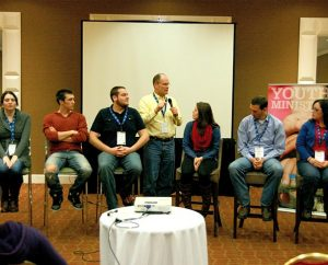 """Director of Christian Education Dr. Craig Oldenburg, standing, asks a panel of six """"emerging adults"""" at the Youth Ministry 2014 (YM14) Symposium to share their faith-formation stories by highlighting the importance of relationships and the role of their local congregations. From left, the panelists are Alex Wright, Tim Anas, Taylor Relle, Thomas Senter and Carlea Halverson. Not shown in the cropped photo is panelist Laura Davis. (LCMS Youth Ministry/Amy Gray)"""