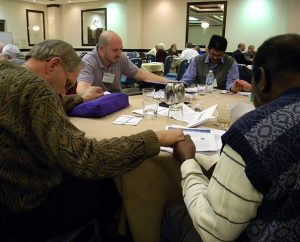 The Rev. Jacob Gillard of the World Mission Prayer League, second from left, leads a prayer during a table discussion at this year's conference of the Association of Lutheran Mission Agencies. (LCMS Communications/Paula Schlueter Ross)