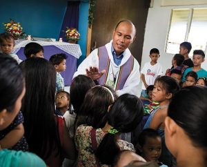 The Rev. Xavier James Palattao blesses children during worship at Christ Lutheran Church in Mahayag, Philippines. (LCMS Communications/Erik M. Lunsford)