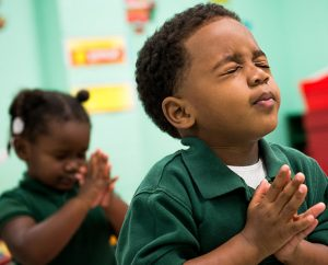Preschooler LaTerry Kennedy prays during school at Trinity Evangelical Lutheran School.