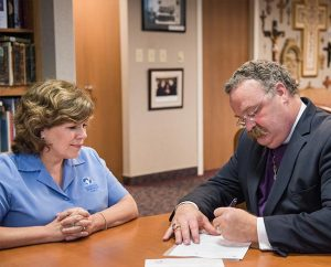LCMS President Rev. Dr. Matthew C. Harrison signs a Memorandum of Understanding May 14, 2014, with Patti Garibay, national executive director of American Heritage Girls, at the Synod's International Center in St. Louis. (LCMS Communications/Erik M. Lunsford)