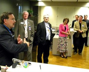 """Synod First Vice-President Rev. Dr. Herbert C. Mueller Jr. (left) thanks the LCMS Board of Directors and staff gathered during the Board's May 16-17 meeting to wish him """"happy birthday"""" on the first day of the meeting. Mueller also spoke of his upcoming open-heart surgery the following week that was considered to be successful. Pictured, from left, are Board member James Carter, LCMS Chief Financial Officer Jerald C. Wulf, Board members Kathy Schulz, Kurt Senske and Ed Everts, and the Rev. Dr. Jon Vieker, senior assistant to the Synod president. (LCMS Communications/Joe Isenhower Jr.)"""