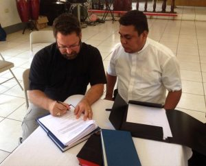 The Rev. Dr. Albert B. Collver III, director of LCMS Church Relations and Regional Operations, left, and Lutheran Church—Synod of Nicaragua President Rev. Marvin Donaire sign a protocol agreement May 13 in Chinandega, Nicaragua. Also signing the document, which allows for expansion of mission work in that country, was the Rev. Leonardo Neitzel, a representative of Lutheran Church—Canada. (LCMS Church Relations)