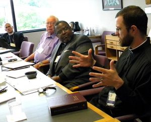 The Rev. Heath R. Curtis describes the current approach of Stewardship Ministry to the LCMS Board for National Mission (BNM) at its May 30-31 meeting. Listening to Curtis, coordinator for the Office of National Mission — Stewardship Ministry, are (from left) BNM members Rev. Steven Briel, Ernest E. Garbe and Rev. Samuel Cosby. (LCMS/Joe Isenhower Jr.)
