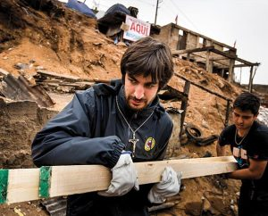 The Rev. Juan Pablo Lanterna, left, of the Confessional Lutheran Church of Chile, and a worker carry building supplies up a fire-scarred hillside in Valparaiso, Chile. (LCMS Communications/Erik M. Lunsford)