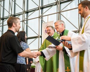 Missionary Michael Ritzman, left, shakes hands with the Rev. Randy Golter, executive director of the LCMS Office of International Mission (OIM), during the June 27 Service of Sending for new missionaries at the International Center chapel. Also pictured are Ritzman's wife, Beth, LCMS President Rev. Dr. Matthew C. Harrison and the Rev. Dr. Edward Grimenstein, OIM's associate executive director. The Ritzmans will serve in Papua New Guinea. (LCMS/Erik M. Lunsford)