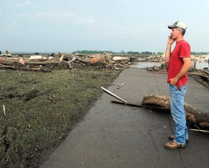 Brian Reeg of Winside, Neb., talks on his phone as he stands on the sidewalk leading to where St. John Lutheran Church stood before being destroyed by a tornado in Pilger, Neb., on June 16, 2014. Reeg has attended the church all his life, and was baptized and married there. A storm packing rare dual tornadoes tore through the tiny farming town in northeast Nebraska, killing a 5-year-old girl, leaving grain bins crumpled like discarded soda cans and flattening dozens of homes. (AP Photo/The Norfolk Daily News, Darin Epperly)