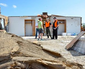 The Rev. Michael Meyer, manager of LCMS Disaster Response, and the Rev. James Carretto, talk with volunteers June 18, 2014, in front of what's left of the parsonage at St. John Lutheran Church in Pilger, Neb. Deadly twin tornadoes ripped through the small community on June 16, damaged about 75 percent of the town. (LCMS Communications/Al Dowbnia)