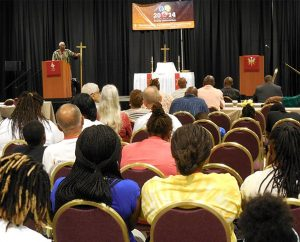 """The Rev. Dr. Victor Belton leads the convocation's opening devotion on July 10. The power of Jesus Christ """"is in you,"""" he told worshipers. """"Confess with your mouth"""" what you """"believe in your heart"""" — that """"Christ died for you … and for all."""" (LCMS/Paula Schlueter Ross)"""