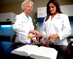 Concordia University Wisconsin School of Pharmacy Professor Dr. Elizabeth Musil, left, and student Janelle Juul mix chemicals in one of the school's clinical research labs. Juul is one of 67 students who graduated from the pharmacy school in May. (Concordia University Wisconsin Marketing Department)